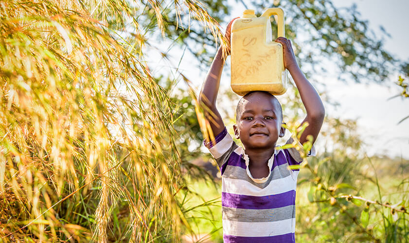 boy carrying a jug of water