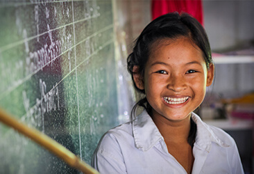 a girl smiling in a classroom
